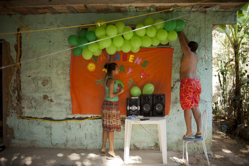 In this Sept. 15, 2012 photo, Thiago Dutra, right, helps hang balloons for the birthday of his wife Thayara Domiciano, left, at their home in the Quilombo Sacopa in Rio de Janeiro, Brazil. Quilombos are communities founded by escaped slaves or their descendents, and in Sacopa, the community is trying to save the grouping of brick houses and shacks nestled in the lush foilage of Brazil's coastal rainforest where families have made their home for more than century but never legally owned. (AP Photo/Victor R. Caivano)