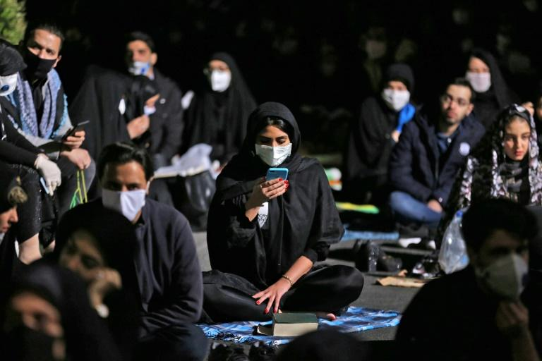 Iranians, some wearing face masks against the coronavirus, attend prayers outside a Tehran mosque on one of the holiest nights of the Muslim fasting month of Ramadan