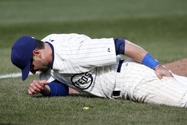 Chicago Cubs right fielder Justin Ruggiano holds his leg in the ninth inning of a baseball game against the Arizona Diamondbacks at Wrigley Field in Chicago on Wednesday, April 23, 2014. (AP Photo/Andrew A. Nelles)