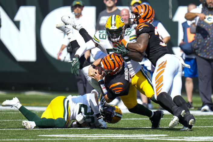 Cincinnati Bengals quarterback Joe Burrow (9) is tackled by Green Bay Packers inside linebacker De'Vondre Campbell (59) and free safety Darnell Savage (26) in the first half of an NFL football game in Cincinnati, Sunday, Oct. 10, 2021. (AP Photo/AJ Mast)