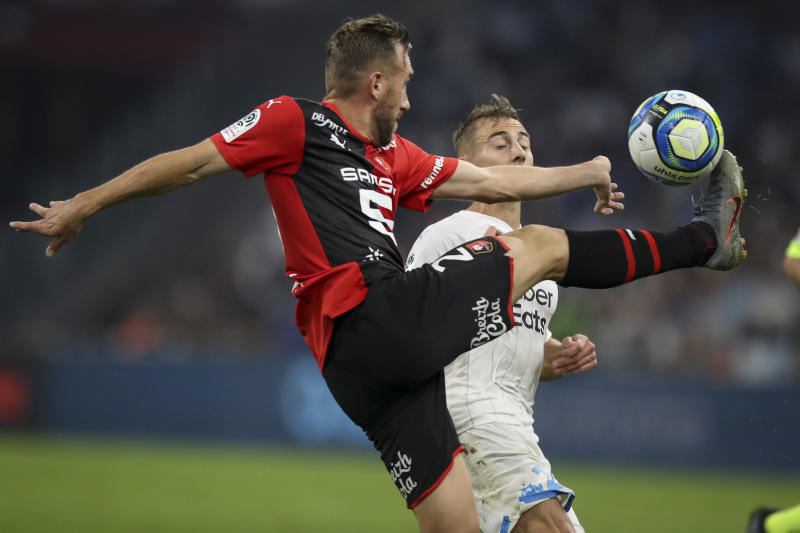Rennes' Flavian Tait and Marseille's Valentin Rongier battle for the ball during the French League One soccer match between Marseille and Rennes at the Velodrome stadium in Marseille, southern France, Sunday, Sept. 29, 2019. (AP Photo/Daniel Cole)