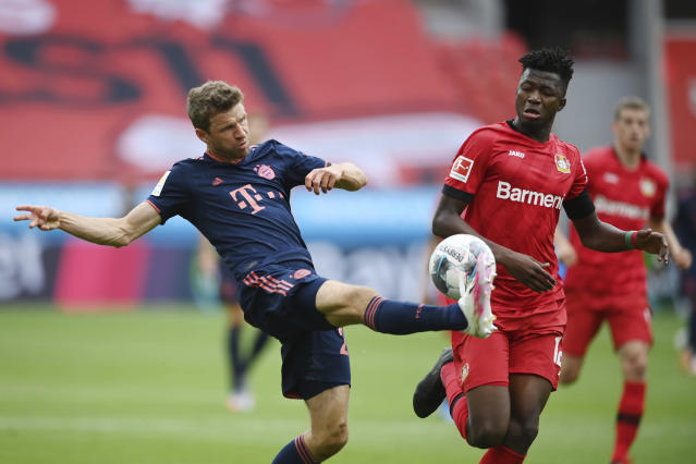 Thomas Mueller, left, of Munich is challenged by Edmond Tapsoda of Leverkusen during the German Bundesliga soccer match between Bayer Leverkusen and Bayern Munich in Leverkusen, Germany, Saturday, June 6, 2020. (Matthias Hangst, Pool via AP)