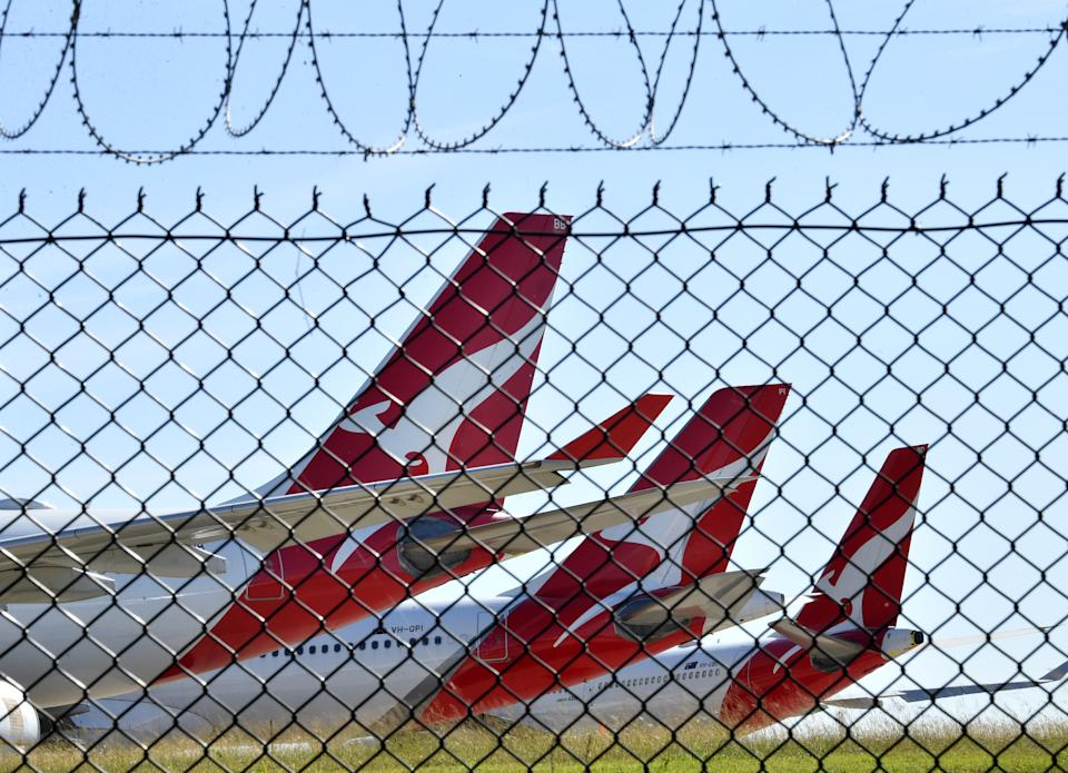 Grounded Qantas aircraft are seen parked at Brisbane Airport in Brisbane, Friday, April 17, 2020. The Australian government has forced airline carriers to cut both their domestic and international flights in order to slow the spread of the coronavirus (COVID-19) disease. (AAP Image/Darren England) NO ARCHIVING
