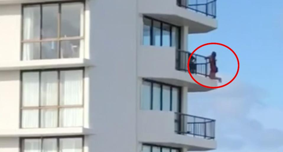 A red circle around a woman shows her clinging on to a high-rise balcony railing.