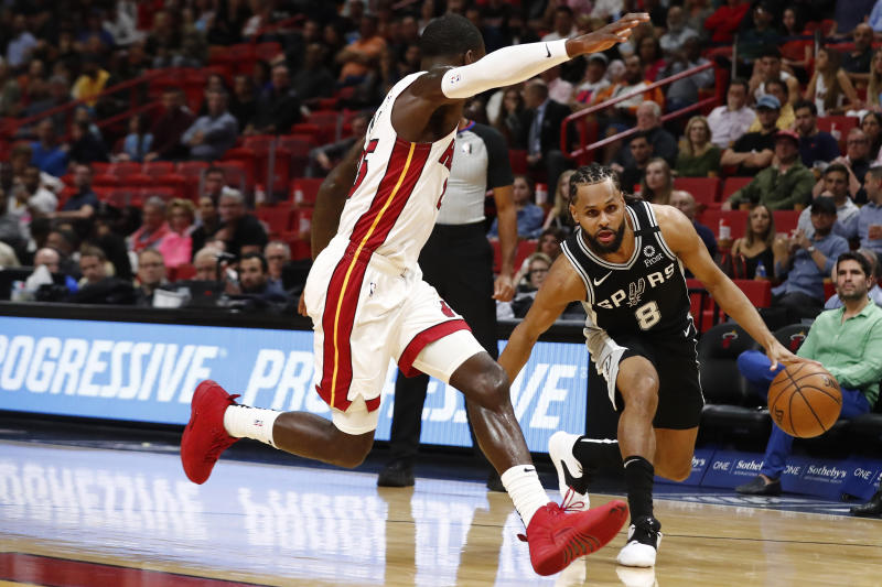 San Antonio Spurs guard Patty Mills (8) dribbles the ball against Miami Heat guard Kendrick Nunn (25) in the first half of an NBA basketball game against the Wednesday, Jan. 15, 2020, in Miami. (AP Photo/Brynn Anderson)