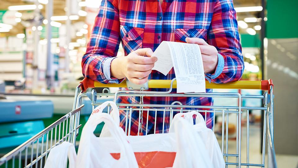 person looking at grocery receipt