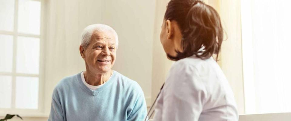 Man with white hair, smiling, talking to doctor in white coat