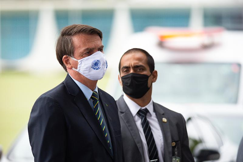 BRASILIA, BRAZIL - MAY 20: President of Brazil Jair Bolsonaro, wearing a face mask with a print of Brazil's Coat of Arms, talks to supporters of his government who waited for him outside the Palácio do Alvorada amidstthe coronavirus (COVID-19) pandemic on May 20, 2020 in Brasilia. Brazil has over 271,000 confirmed positive cases of Coronavirus and 17,971 deaths. (Photo by Andressa Anholete/Getty Images)