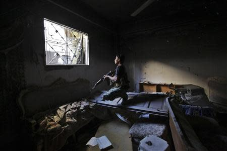 A Free Syrian army fighter carries his weapon in a damaged building in Jubaila neighbourhood in Deir al zor, eastern Syria