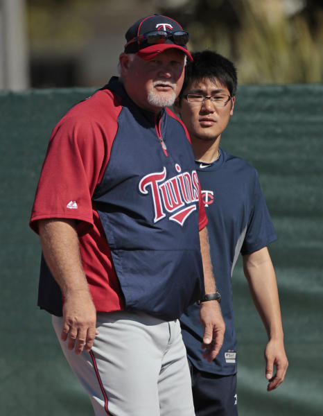 FILE - In this Feb. 23, 2011 file photo, Japanese interpreter Ryo Shinkawa, rear, stands ready to help as Minnesota Twins Manager Ron Gardenhire watches his players during a spring training baseball workout at the Hammond Stadium complex in Fort Myers, Fla. A new rule in Major League Baseball that lets interpreters join managers and coaches on the mound when pitchers aren't fluent in English might still need some tweaking. The rule has already been used in spring training. (AP Photo/Dave Martin, File)