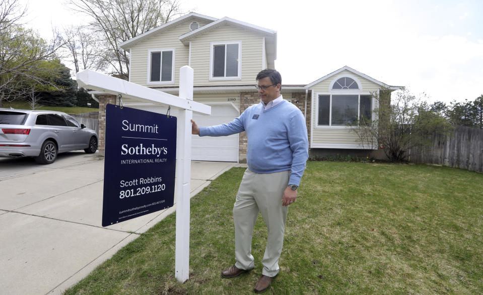 In this April 13, 2019, photo, real estate agent Scott Robbins stands in front of a home, in suburban Salt Lake City. Home prices in the greater Salt Lake City area have surged 8% in the past year Robbins, president of the Salt Lake Board of Realtors, sees the price growth as having changed the habits of first-time buyers. (AP Photo/Rick Bowmer)