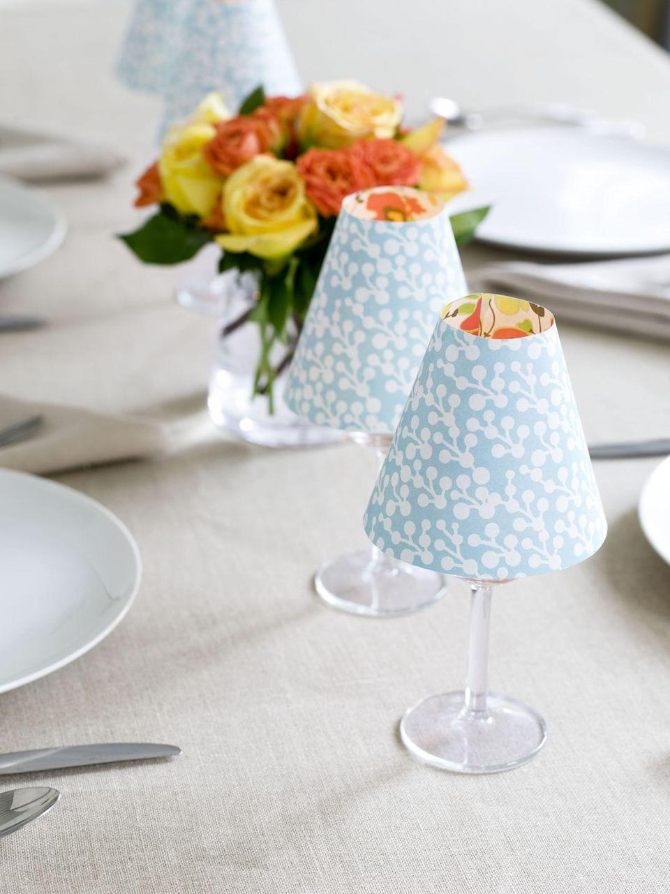 """<p>The dinner table shines brighter with a few clever """"lamps."""" Just pop a LED tea light in a wine glass and top it with a paper shade. </p><p><em><a href=""""https://www.goodhousekeeping.com/home/craft-ideas/how-to/a19133/candle-lampshade-craft/"""" rel=""""nofollow noopener"""" target=""""_blank"""" data-ylk=""""slk:Get the tutorial »"""" class=""""link rapid-noclick-resp"""">Get the tutorial »</a></em> </p>"""