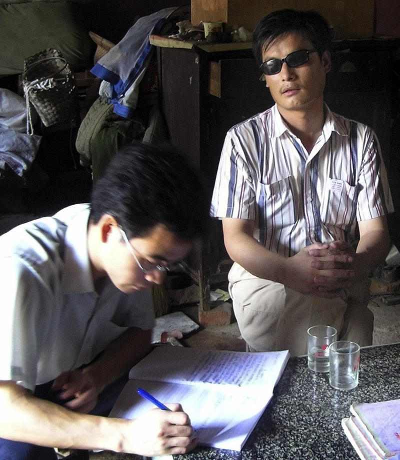 """FILE - In this undated file photo released by his supporters, blind activist Chen Guangcheng, right sits in a village in China.  Rights activists have criticized a Hollywood studio for filming a buddy comedy in an eastern Chinese city where the blind, self-taught activist lawyer is being held under house arrest and reportedly beaten.  Relativity Media is shooting part of the comedy """"21 and Over"""" in Linyi, a city in Shandong province where the activist Chen's village is located. Authorities have turned Chen's village of Dongshigu into a hostile, no-go zone and activists, foreign diplomats and reporters have been turned back, threatened and had stones thrown at them by men patrolling the village. (AP Photo/Supporters of Chen Guangcheng, File)"""