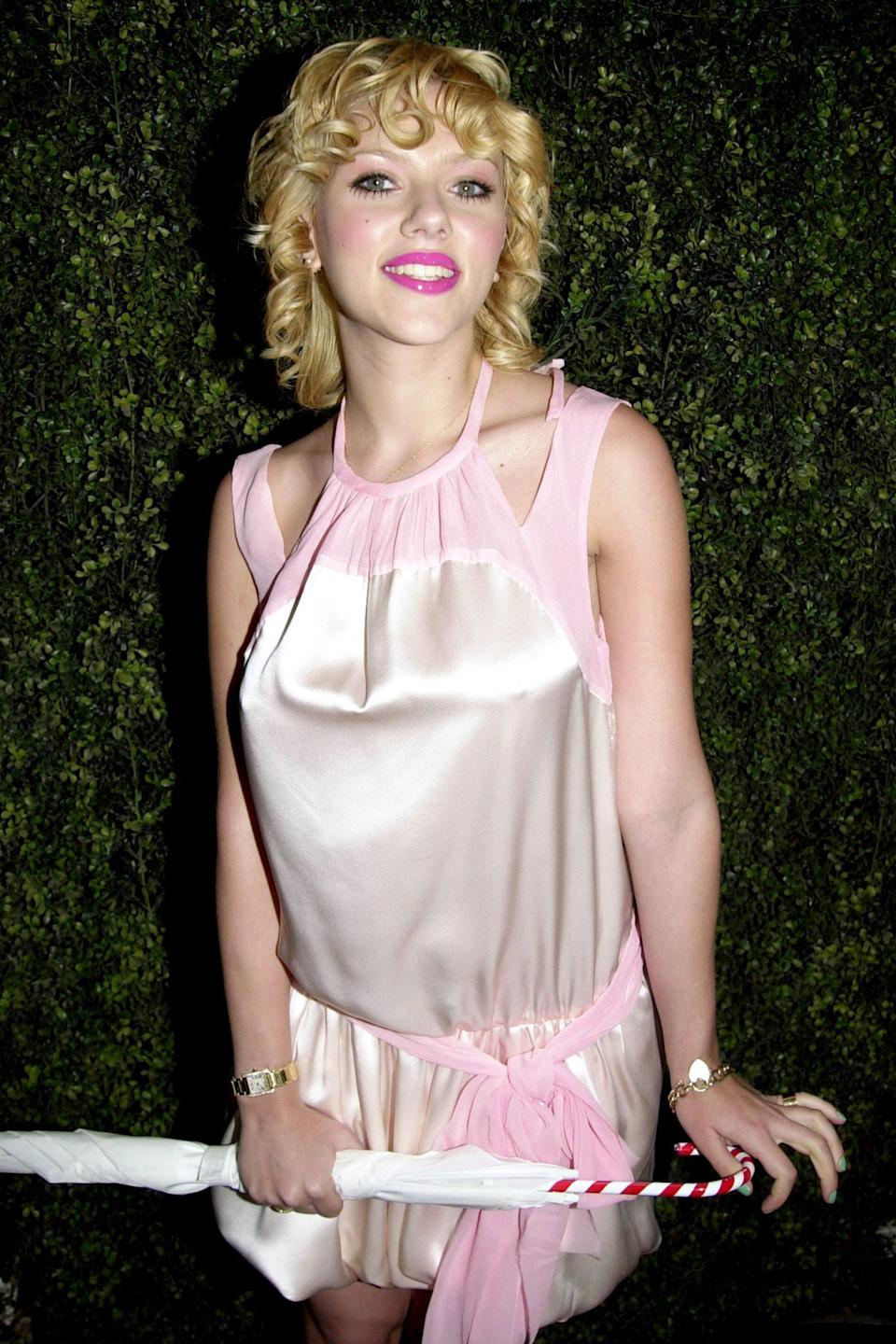 <p>Barrel curls, pink lips and a candy-striped parasol all added to the doll-like vibes she rocked at Cynthia Rowley's 2004 fashion show.</p>
