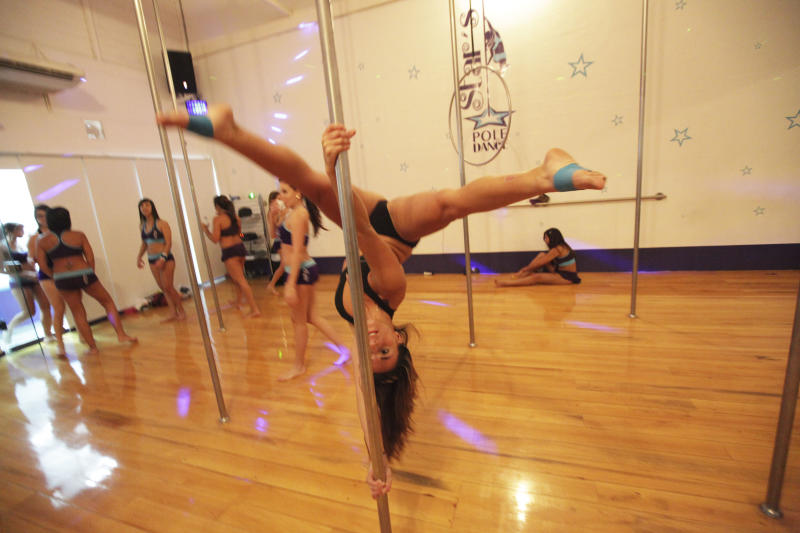 In this photo taken July 11, 2012. A pole dancer perform during a practice session of pole dancing at a gym in Caracas, Venezuela. Pole dancing may have started out in strip clubs, but since the 1990s, it's become an all-ages exercise and sport phenomenon the world over. Now, it's hit the streets in Venezuela, a country that's made beauty and fitness a cult and minted more Miss Universes than any other except the United States. (AP Photo/Fernando Llano)