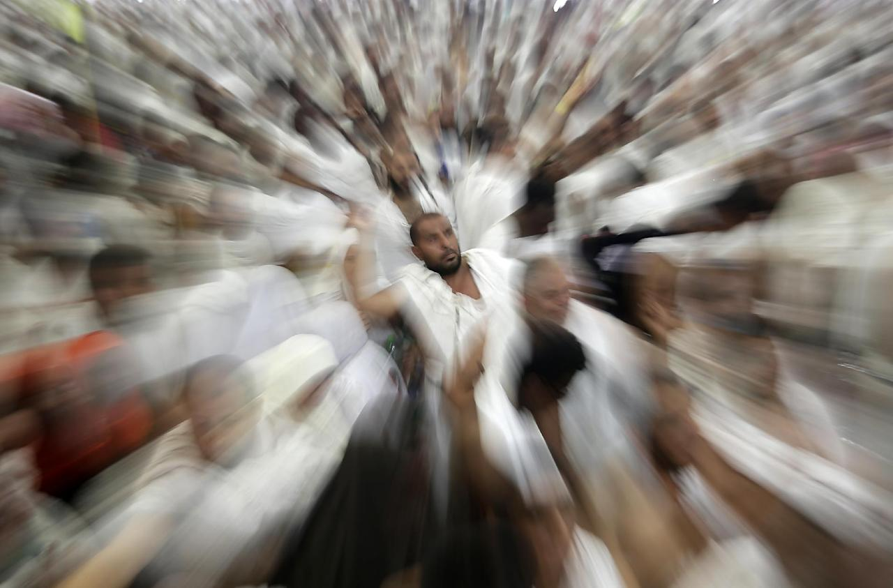 """In this image made while zooming the camera lens, Muslim pilgrims cast stones at a pillar, symbolizing the stoning of Satan, in a ritual called """"Jamarat,"""" a rite of the annual hajj, the Islamic faith's most holy pilgrimage, in Mina near the Saudi holy city of Mecca, Saudi Arabia, Friday, Oct. 26, 2012. The five-day rituals of Hajj began on October 24 when millions arrived in the holy city of Mecca and continues for another two days. (AP Photo/Hassan Ammar)"""