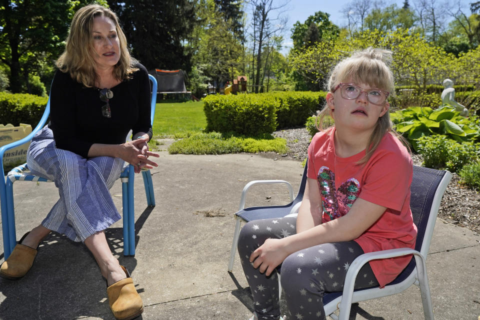 Holly Christensen, left, talks with her daughter, Lyra, Thursday, May 13, 2021, in Akron, Ohio. Anti-abortion activists say 2021 has been a breakthrough year for legislation in several states seeking to prohibit abortions based on a prenatal diagnosis of Down syndrome. Opponents of the bills, including some parents with children who have Down syndrome like Holly, argue that elected officials should not be meddling with a woman's deeply personal decision on whether to carry a pregnancy to term after a Down syndrome diagnosis. (AP Photo/Tony Dejak)