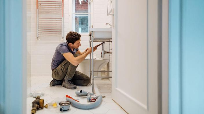 Young man fixing a leak under the bathroom sink.