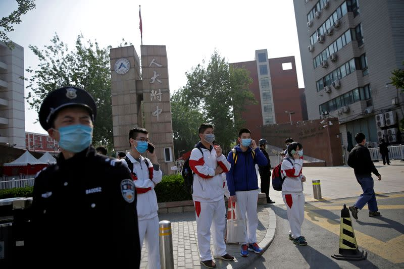 FILE PHOTO: Students wearing face masks leave a school in Beijing