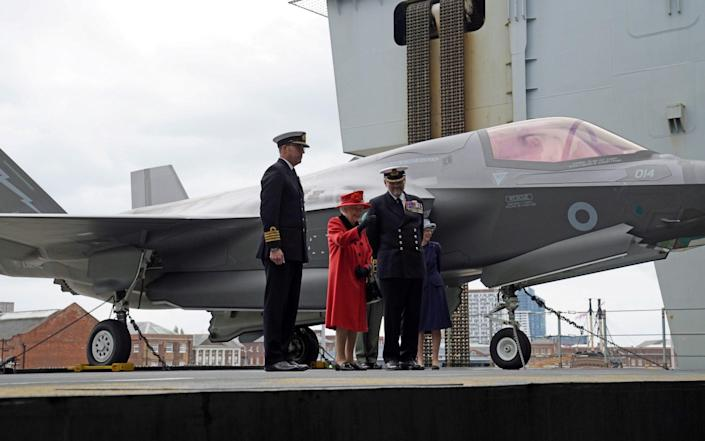 Captain Angus Essenhigh (CO of HMS Queen Elizabeth) and Commodore Steve Moorhouse (Commander of the Carrier Strike Group) hosted The Queen on the £3bn ship. May 22, 2021. - REUTERS