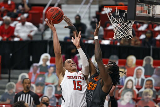 Texas Tech's Kevin McCullar (15) shoots over Oklahoma State's Kalib Boone (22) during the first half of an NCAA college basketball game Saturday, Jan. 2, 2021, in Lubbock, Texas. (AP Photo/Brad Tollefson)