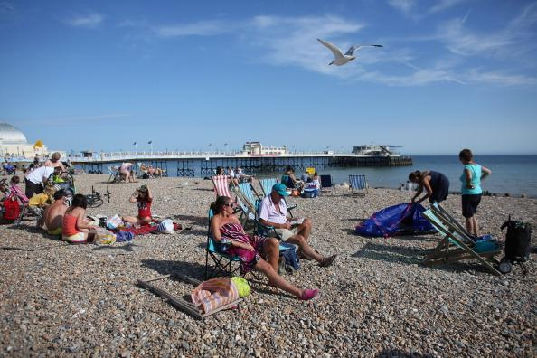 Members of the public enjoy the warm weather at the seaside on August 18, 2012 in Worthing, England. Many areas of the UK are experiencing the hottest day of the year so far, with some parts seeing the temperature exceed 32 degrees Celsius. (Photo by Oli Scarff/Getty Images)