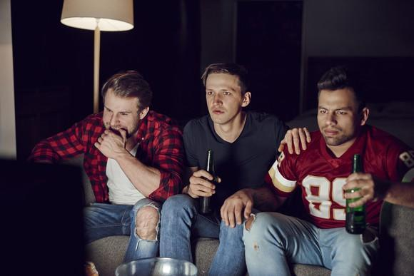 Three men, including one in a football jersey, sit on a sofa in front of a TV while drinking beer.