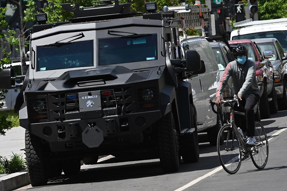 A cyclist rides pass an armoured vehicle heading towards Lafayette Square on 16th Street, as people protest the death of George Floyd, an unarmed black man who died while while being arrested and pinned to the ground by the knee of a Minneapolis police officer, in Washington, DC on June 1, 2020. - Police fired tear gas outside the White House late Sunday as anti-racism protestors again took to the streets to voice fury at police brutality, and major US cities were put under curfew to suppress rioting.With the Trump administration branding instigators of six nights of rioting as domestic terrorists, there were more confrontations between protestors and police and fresh outbreaks of looting. Local US leaders appealed to citizens to give constructive outlet to their rage over the death of an unarmed black man in Minneapolis, while night-time curfews were imposed in cities including Washington, Los Angeles and Houston. (Photo by Mandel NGAN / AFP) (Photo by MANDEL NGAN/AFP via Getty Images)