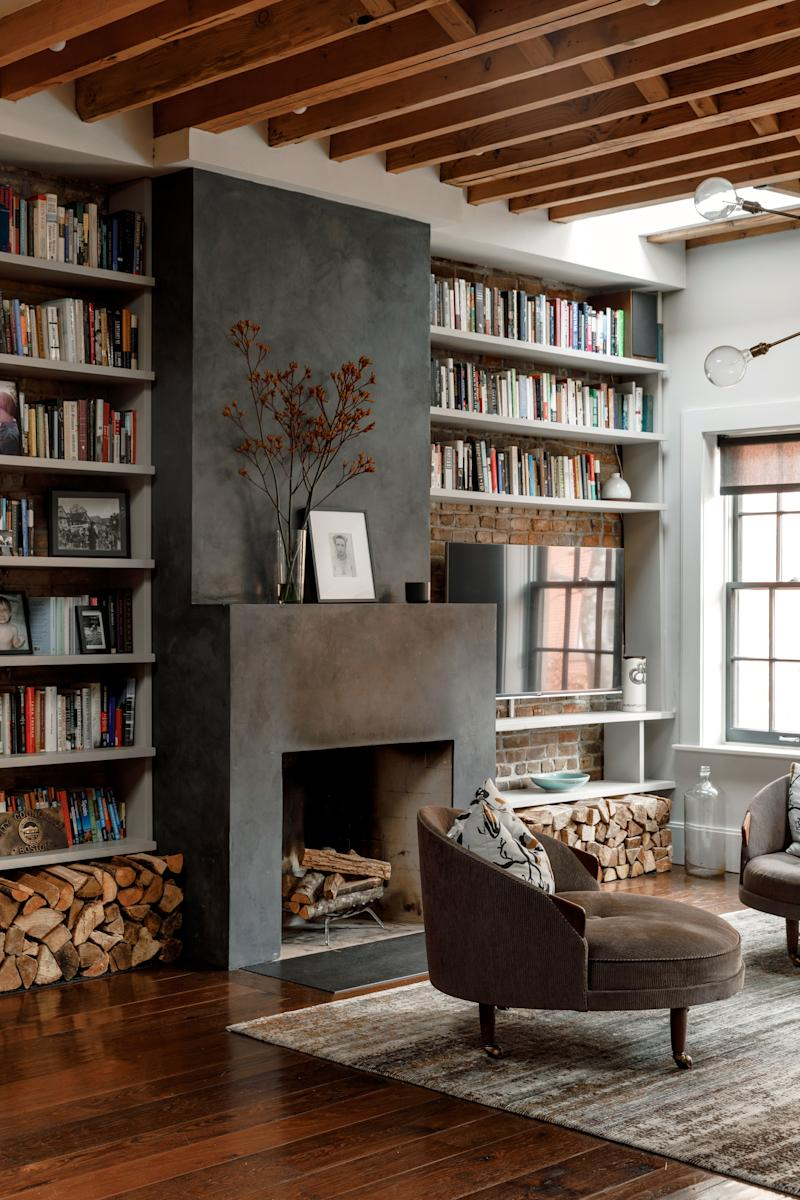 The fireplace in the living area was one of the things that convinced Tierney to buy the house. Originally brick, it was given a sleek plaster makeover by Kamp Studios' Kim Collins. Work by Cindy Sherman rests atop it.