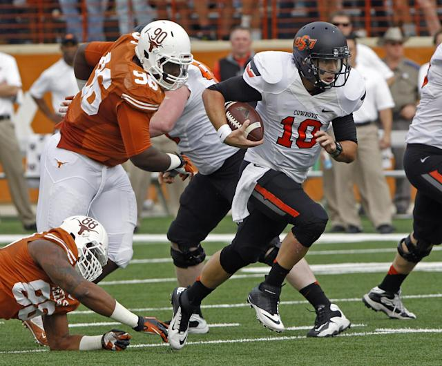 Oklahoma State's2 Clint Chelf (10) runs for a first down against Texas defensive linemen Cedric Reed (88) and Malcom Brown (90) during the first quarter of an NCAA college football game Saturday, Nov. 16, 2013, in Austin, Texas. (AP Photo/Michael Thomas)