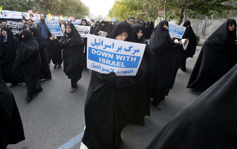 In this picture taken on Friday, Nov. 16, 2012, an Iranian female worshipper holds an anti-Israeli placard, in a pro-Palestinian demonstration after Friday prayer, in Tehran, Iran. (AP Photo/Vahid Salemi)