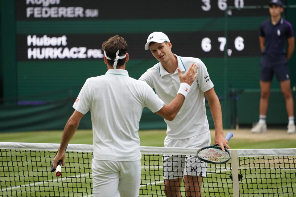Switzerland's Roger Federer greets Poland's Hubert Hurkacz at the end of the men's singles quarterfinals match on day nine of the Wimbledon Tennis Championships in London, Wednesday, July 7, 2021. (AP Photo/Alberto Pezzali)
