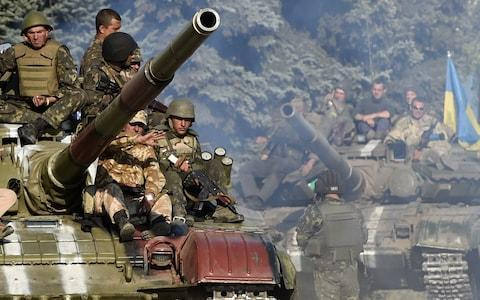 <span>Ukrainian army soldiers ride a tank on a road near where pro-Russian separatists fired heavy artillery</span>