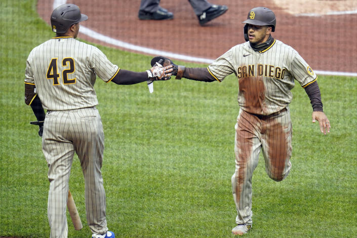 San Diego Padres' Trent Grisham, right, is greeted by an on-deck batter after scoring on a double by Jake Cronenworth in the first inning of a baseball game against the Pittsburgh Pirates, Thursday, April 15, 2021, in Pittsburgh. (AP Photo/Keith Srakocic)
