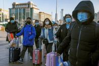 Travellers push suitcases outside Beijing Railway Station following an outbreak of the coronavirus disease (COVID-19) in Beijing