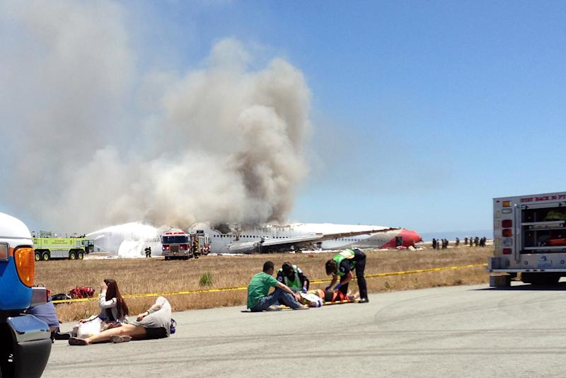 FILE - In this Saturday, July 6, 2013, file photo provided by passenger Benjamin Levy, passengers from Asiana Airlines flight 214 are treated by first responders on the tarmac just moments after the plane crashed at the San Francisco International Airport in San Francisco. Officials are looking into whether some attorneys may have violated a U.S. law barring uninvited solicitation of air disaster victims in the first 45 days after an accident in connection with the crash landing of Asiana Flight 214 in San Francisco. The National Transportation Safety Board says it has received an unspecified number of complaints about solicitations since the July 6 accident that killed three Chinese teenage girls and injured 180. (AP Photo/Benjamin Levy)
