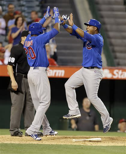 Chicago Cubs Julio Borbon, left, and Luis Valbuena, two of three runners who scored on a an Anthony Rizzo double, celebrate in the tenth inning against the Los Angeles Angels in a baseball game in Anaheim, Calif., Wednesday, June 5, 2013. (AP Photo/Reed Saxon)