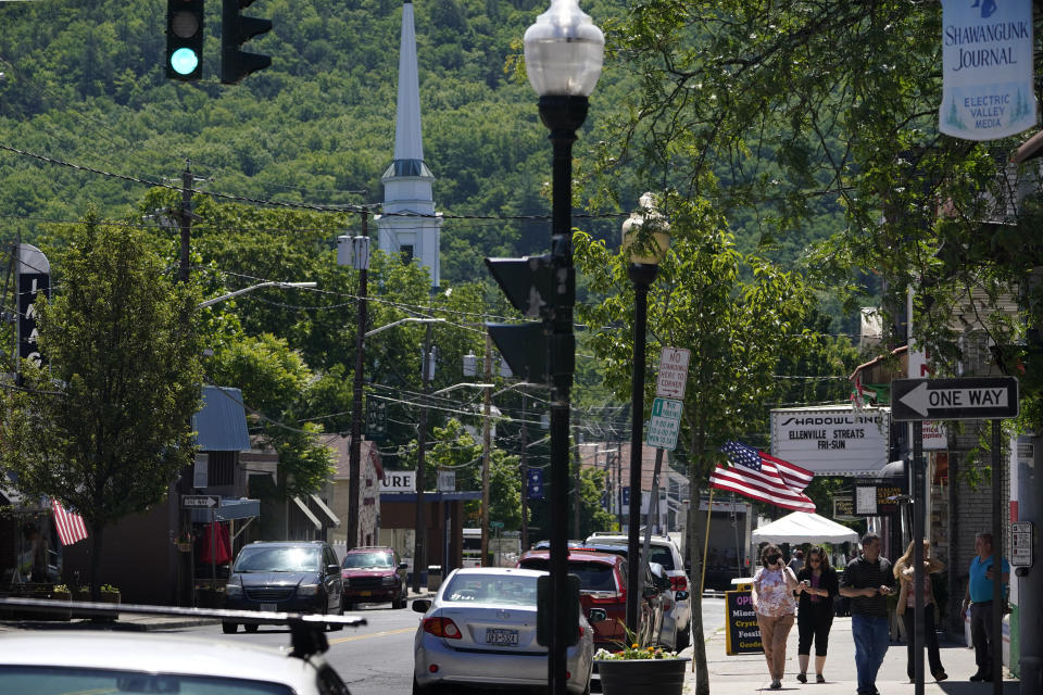 People walk on one of the main streets in Ellenville, N.Y., Wednesday, June 16, 2021. Less than 100 miles north of New York City, Ulster County is popular destination for weekenders headed to Woodstock or the Catskill Mountains. Though pretty, there are pockets of poverty. The county is working with the Center for Guaranteed Income Research at the University of Pennsylvania on a pilot program funded by private donations. One hundred households making less than $46,900 a year in May began receiving a $500 payment each month for a year. Recipients of the money can spend it as they wish, but will be asked to participate in periodic surveys about their physical health, mental health and employment status. (AP Photo/Seth Wenig)