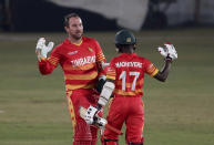 Zimbabwe's batsman Brendan Taylor, left, celebrates with teammate Wessley Madhevere after completing his century during the 1st one-day international cricket match against Pakistan at the Pindi Cricket Stadium, in Rawalpindi, Pakistan, Friday, Oct. 30, 2020. (AP Photo/Anjum Naveed)