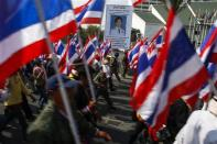 Anti-government protesters march past a poster of Thai Prime Minister Yingluck Shinawatra during a rally in central Bangkok January 24, 2014. REUTERS/Athit Perawongmetha