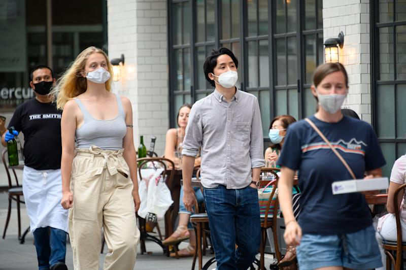 NEW YORK, NEW YORK - JUNE 30: People wear a protective face mask outside The Smith on the Upper East Side as New York City moves into Phase 2 of re-opening following restrictions imposed to curb the coronavirus pandemic on June 30, 2020. Phase 2 permits the reopening of offices, in-store retail, outdoor dining, barbers and beauty parlors and numerous other businesses. Phase 2 is the second of four phased stages designated by the state. (Photo by Noam Galai/Getty Images)