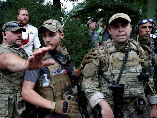 A white supremacists stands behind militia members after he scuffled with a counter demonstrator in Charlottesville, Virginia, U.S., August 12, 2017.