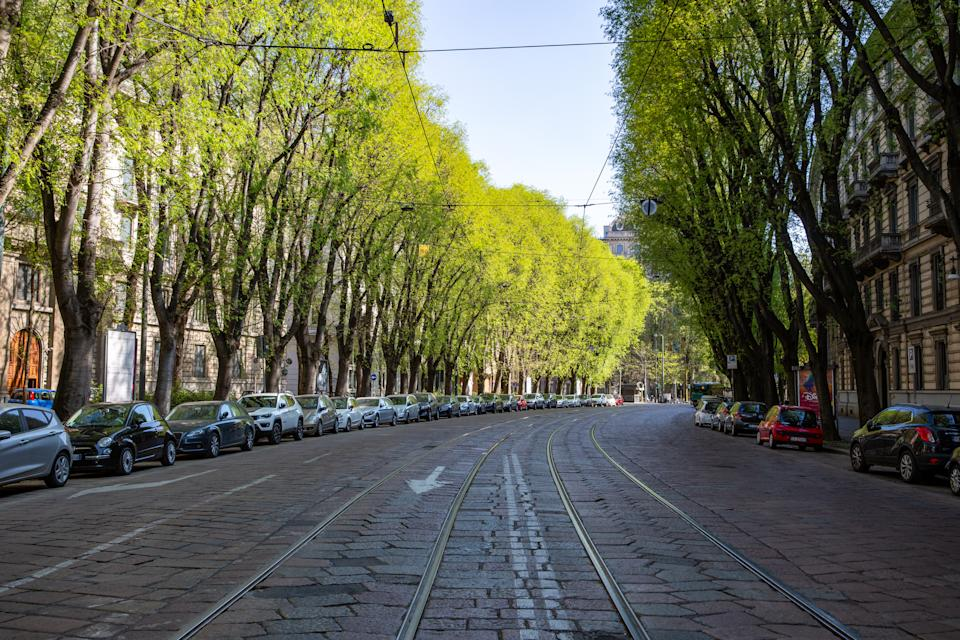 Parked cars line a street devoid of traffic in Milan, Italy in early April. Milan plans to open 22 miles of street to new cycle paths in May and June. (Credit: Francesca Volpi/Bloomberg)