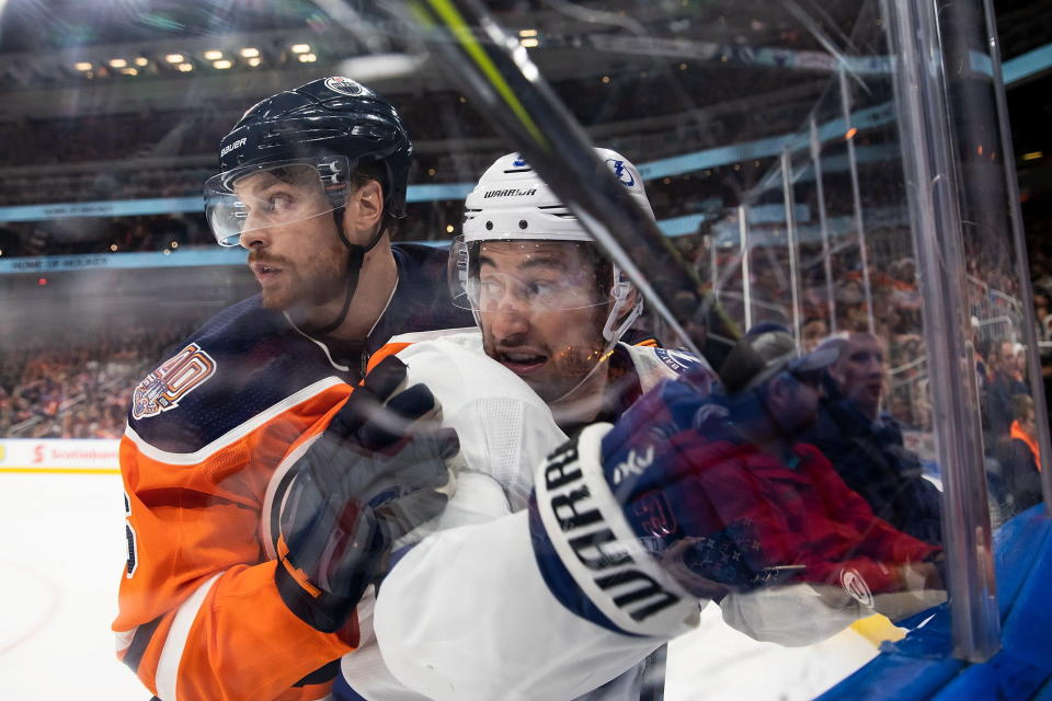 Edmonton Oilers defenseman Adam Larsson (6) holds Tampa Bay Lightning center Tyler Johnson (9) against the boards during the third period of an NHL hockey game Saturday, Dec. 22, 2018, in Edmonton, Alberta. (Codie McLachlan/The Canadian Press via AP)