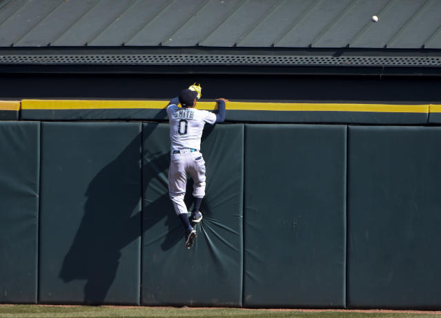 Seattle Mariners center fielder Mallex Smith (0) climbs the wall chasing a home run hit by Chicago White Sox's Tim Anderson (7) during the seventh inning of a baseball game in Chicago, Saturday, April 6, 2019. (AP Photo/Matt Marton)