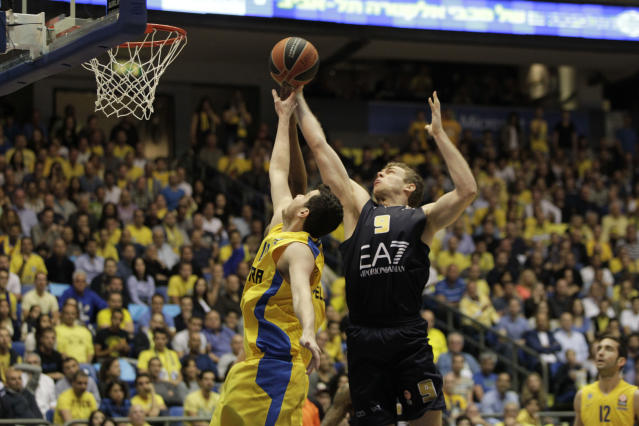 Emporio Armani Milan's Nicolo Melli, right, and Maccbi Tel Aviv's Guy Pnini in action during the EuroLeague Basketball Group D playoffs game in Tel Aviv, Israel, Monday April 21, 2014. (AP Photo/Ariel Schalit)