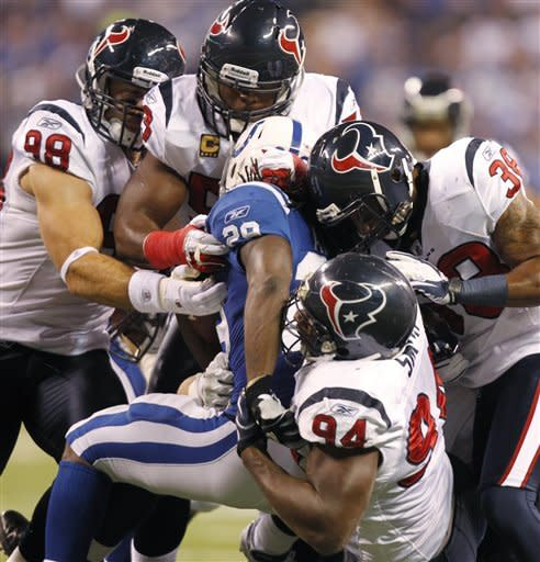 Indianapolis Colts' Joseph Addai is tackled by the Houston Texans defense during the first half of an NFL football game Thursday, Dec. 22, 2011, in Indianapolis. (AP Photo/Michael Conroy)