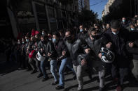 University students wearing protective face masks take part in a rally against education reforms in Athens, Thursday, Feb. 4, 2021. Thousands of protesters in Greece have held demonstrations in the Greek capital and the second largest city of Thessaloniki against plans by the government to police university campuses. (AP Photo/Petros Giannakouris)