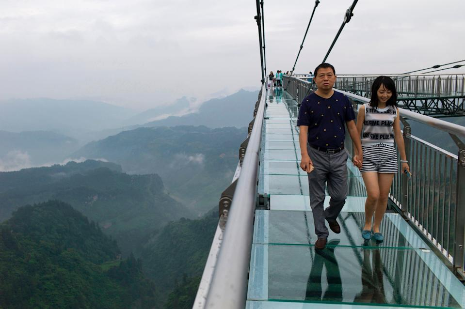 <p>File A glass-bottomed skywalk, certified as the world's longest, at the Ordovician park in Wansheng.  Hovering more than 100 metres (328 feet) above a gaping chasm</p> (AFP via Getty Images)
