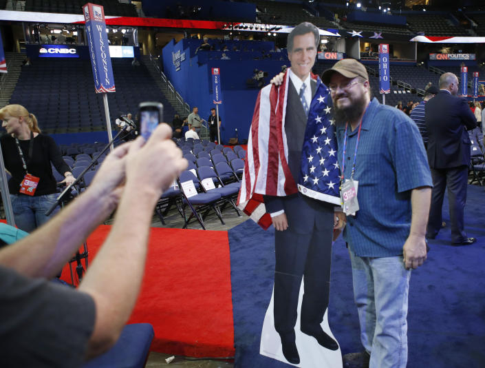 Travis Chapin from St. Petersburg, Fla., poses for a picture with a life-size picture figure of Republican presidential nominee Mitt Romney on the floor at the Republican National Convention in Tampa, Fla., on Wednesday, Aug. 29, 2012. (AP Photo/Jae C. Hong)